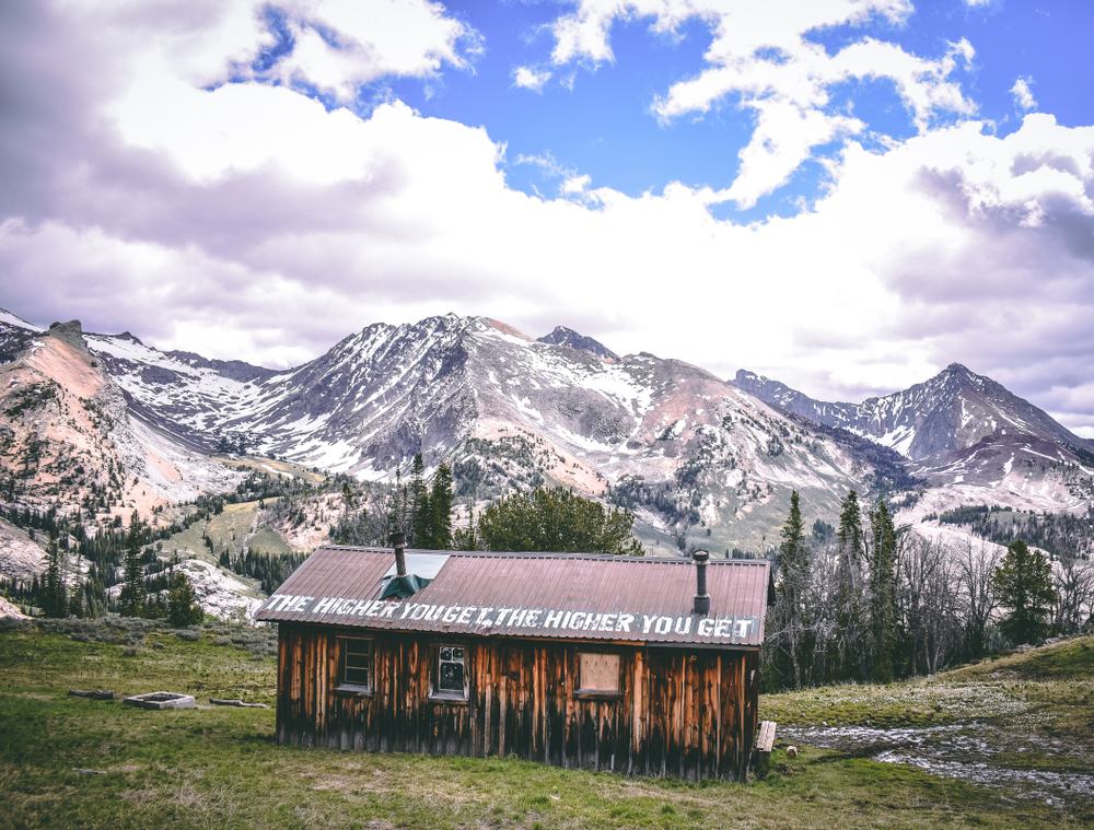 """A building which reads """"the higher you get the higher you get"""" on the roof top, a popular site near Ketchum in the Sun Valley, with mountains and trees in the distance."""