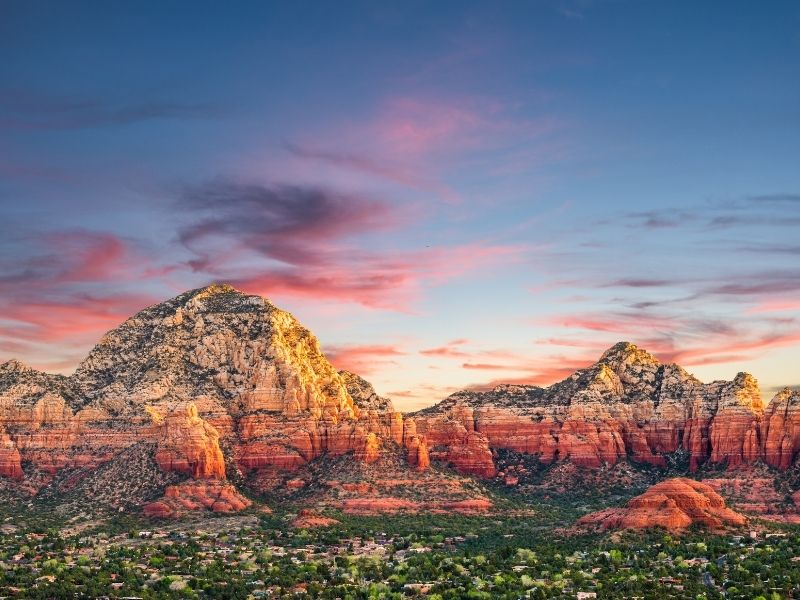 A colorful sunrise over the red rock formations of Sedona and the trees in the valley