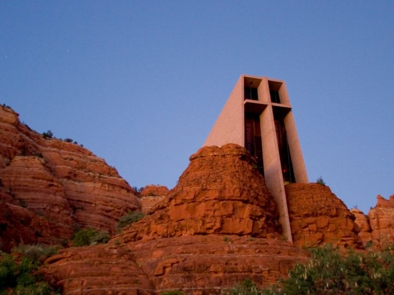 the famous chapel in the rocks of sedona which blends into the natural scenery after dark
