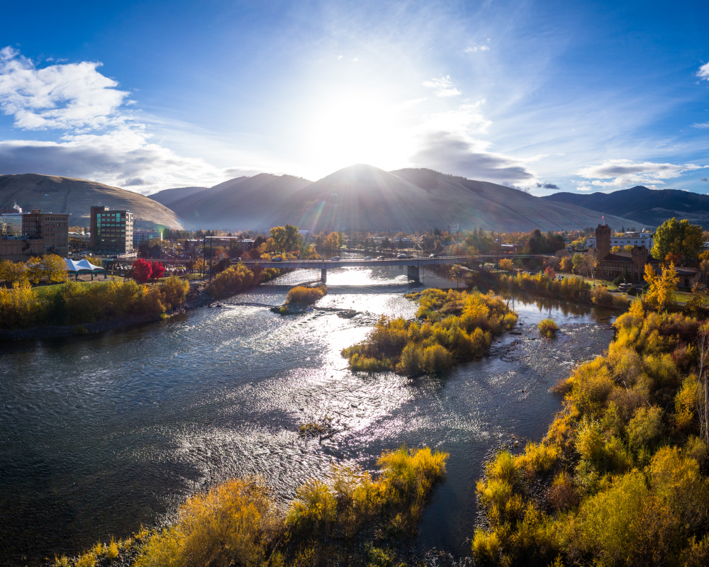 A sunny view of the sun setting below Missoula mountain ranges with some buildings on one side, the river in the middle, a bridge crossing the river, and trees on the other side of the river.