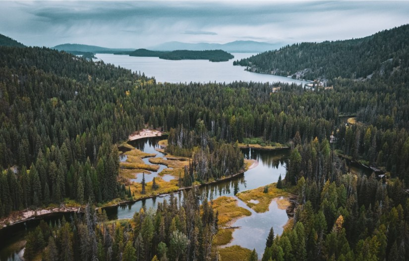 A view of the small marshy lakes and larger lake in the background in McCall Idaho on a cloudy, overcast day.