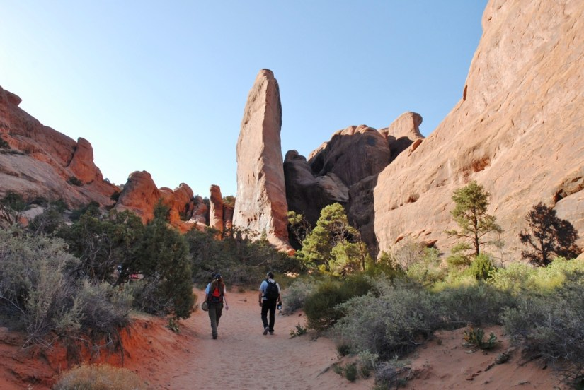 two hikers walking down a trail in the devils garden section of arches national park.