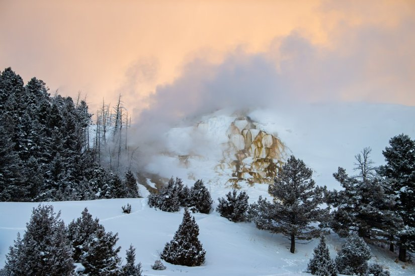 View of Mammoth Hot Springs with orangey-pink sunrise sky and mist floating up from geyser.