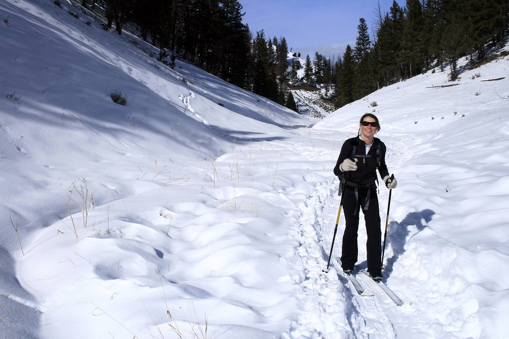 A white woman smiling and going cross-country skiing in Yellowstone national park