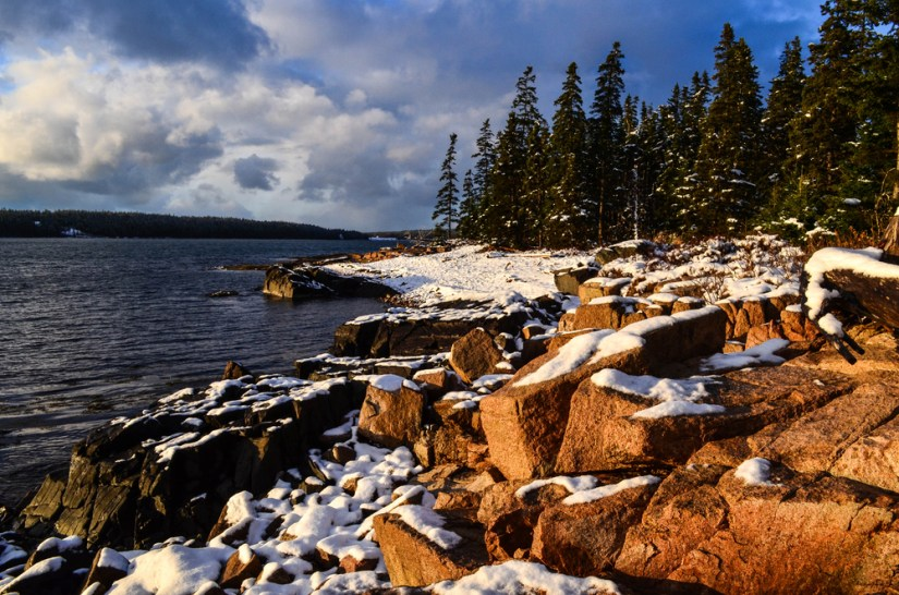 Snow covered rocks with background of Atlantic Ocean and trees.
