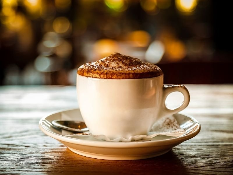 A perfect cappuccino with foam with chocolate on top, served on a wood table.