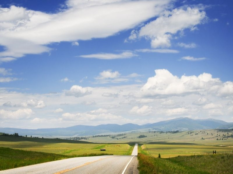 A rolling highway road leading towards Big Sky Montana mountain resort, grassy fields leading to mountains in the distance.