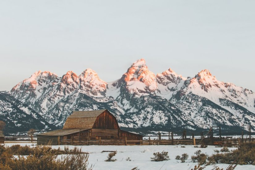 """A view of the famous """"Grand Teton Cabin"""", a wooden structure shaped almost like a sombrero hat, with a sunrise light glow on the tips of the mountain range behind."""