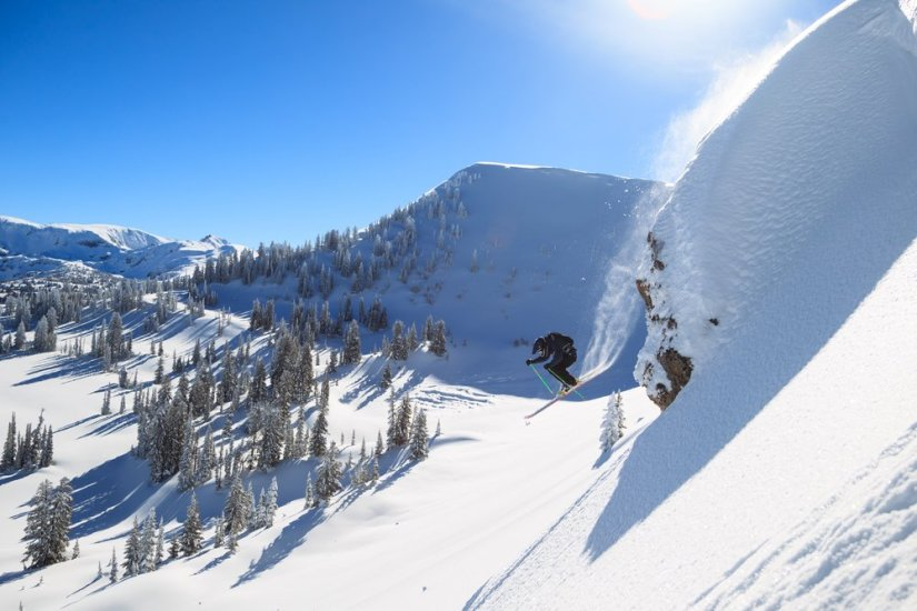 A man skiing doing a large jump in the backcountry landscape of the Grand Tetons with a powder trail behind him.