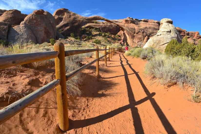 A nearly empty trail in Devils Garden in Arches National Park with red sand on the trail and views of the red rocks and arches around it.