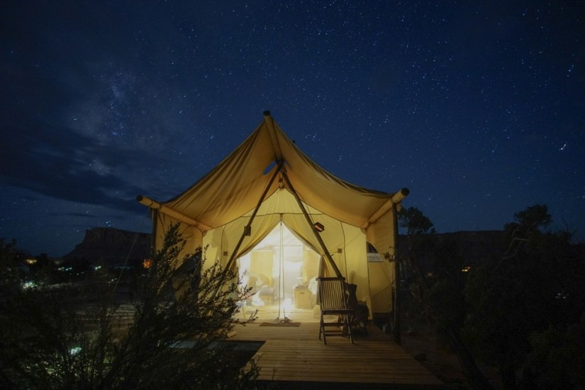 A lit up canvas glamping tent with a dark night sky with lots of visible stars.