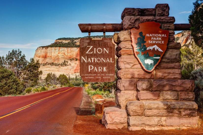 "A sign which reads ""Zion National Park, National Park Service"" on the road leading to the national park with mountains in the background."