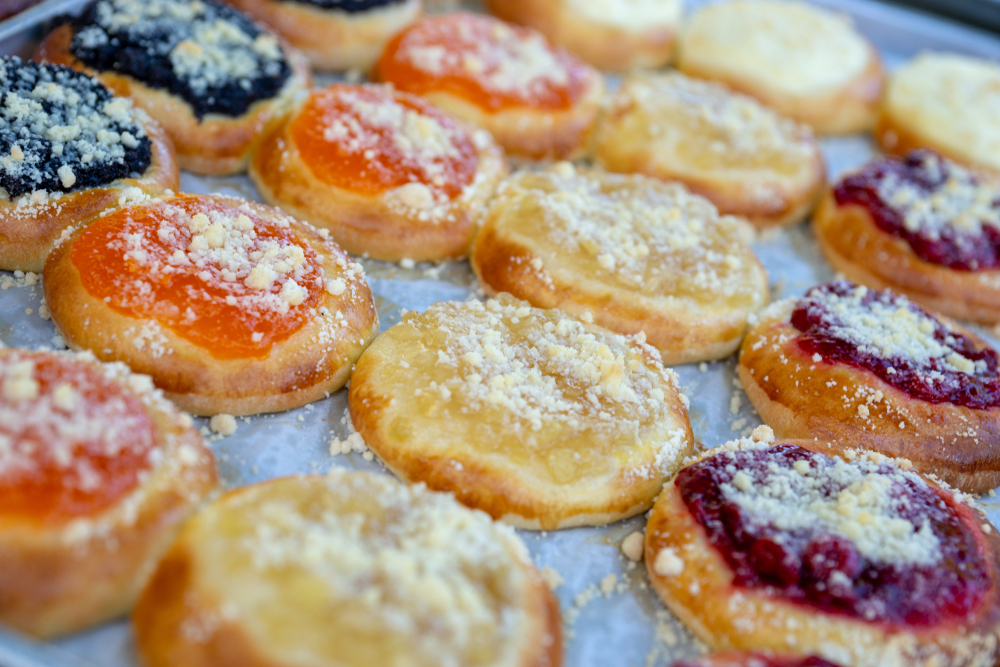 Four different colorful kolache Czech pastries, with black, orange, yellow, and red jams, a great way to start a day in Prague.