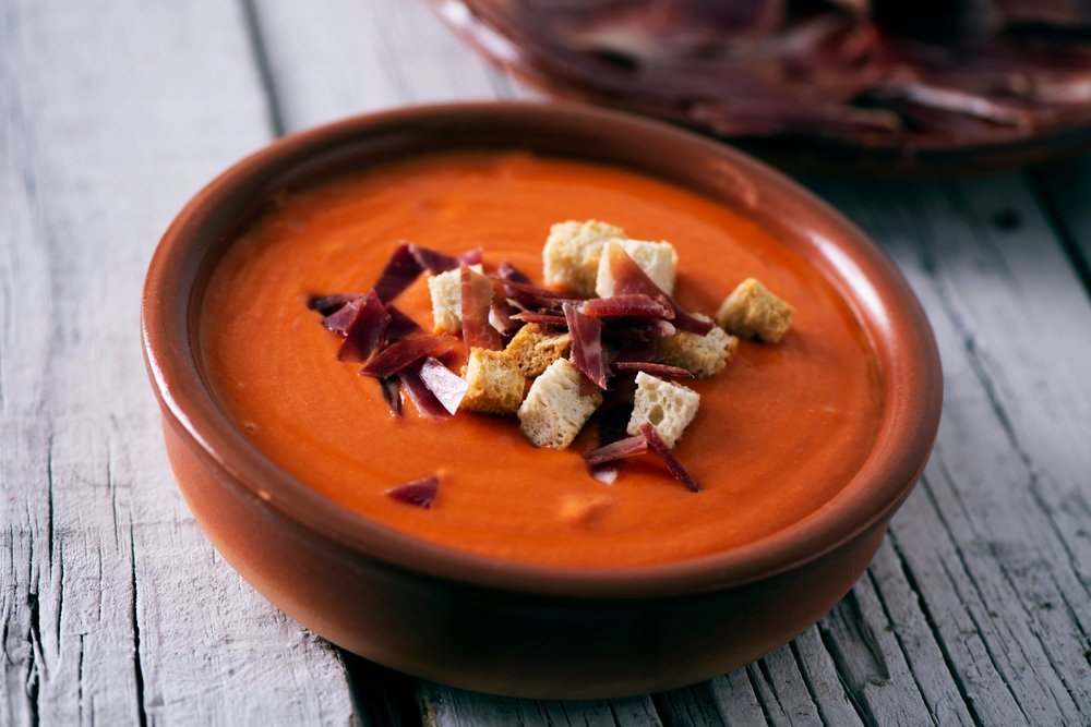 A bowl of red soup topped with meat and croutons at a Spanish restaurant.