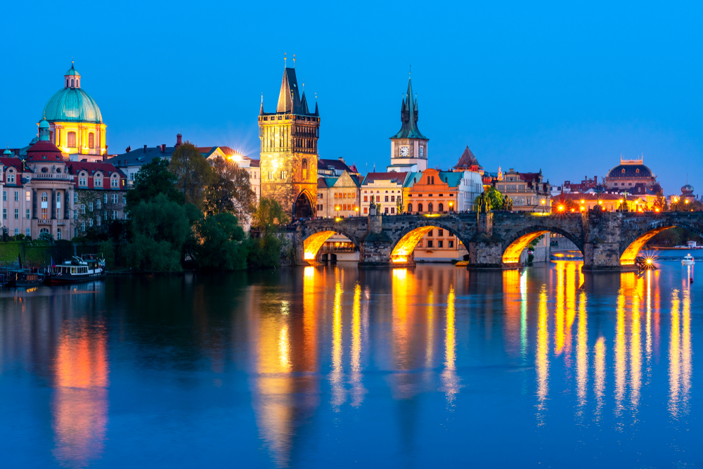 Blue hour in Prague with lots of lights on in the city, reflecting in the water, you can see Charles Bridge, a watchtower, and distinctive Prague architecture in the skyline.