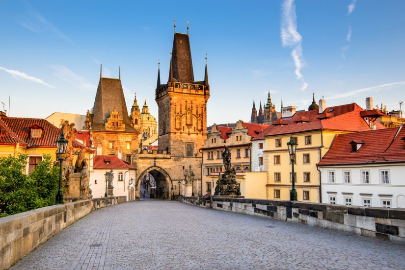 Walking across the Charles Bridge towards Mala Strana and the Castle District, buildings with red roofs on the side and observation towers and a basilica dome in the background.