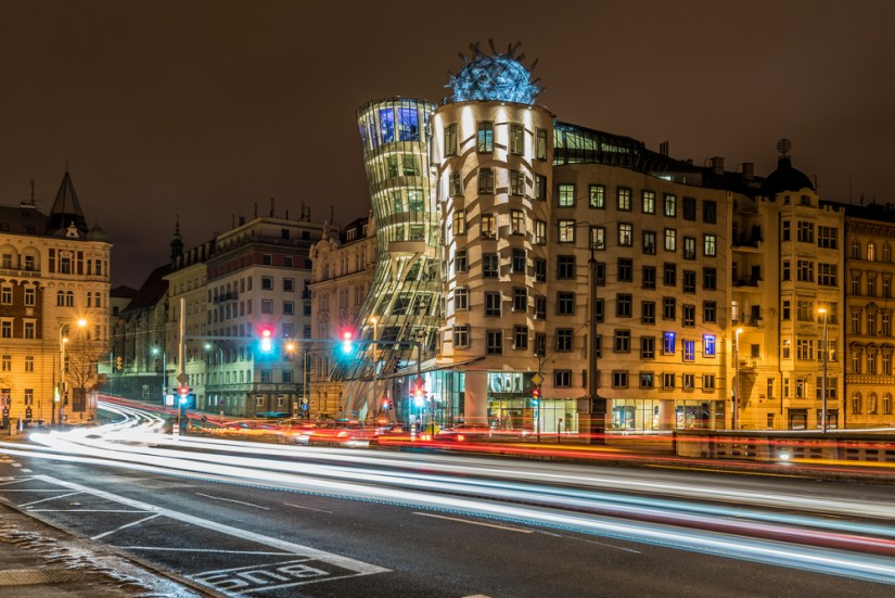 The Dancing House building lit up at night: two buildings intertwined together with  a movement that makes them look like they're dancing, with light trails on the street in the foreground.