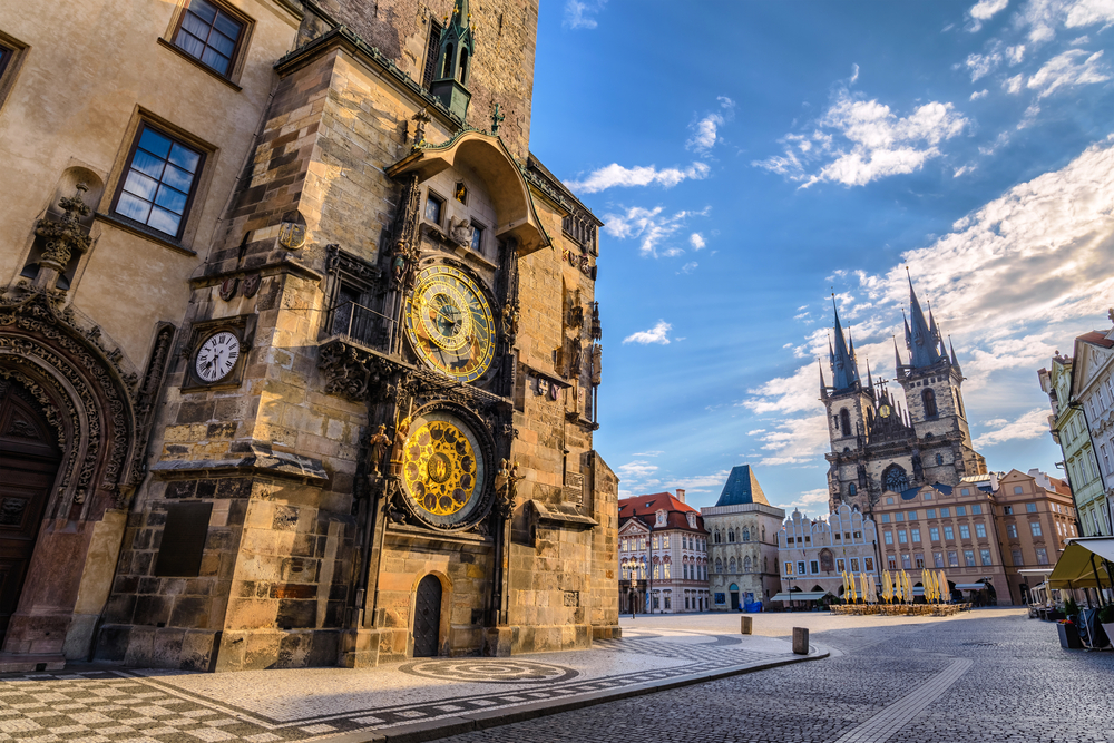 The Old Astronomical Clock with lots of painted detail and on the right side the Our Lady Before Tyn Church with two distinct spires, lots of pastel buildings around the square with cobblestone walkways.