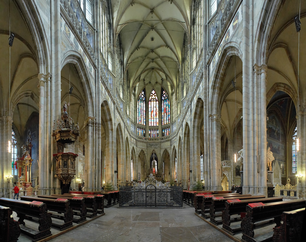 The interior of a cathedral with stained glass and high arch ceilings with rows of pews