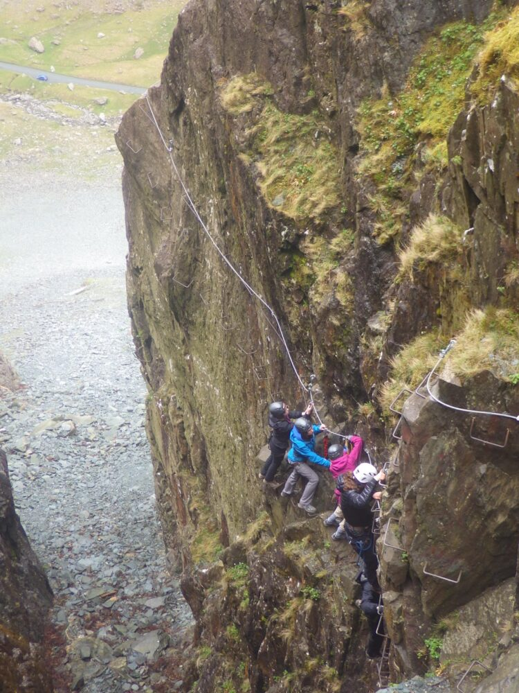 A group of four people climbing on iron ladders and railings (via ferrata) in order to ascend a cliff