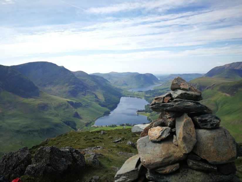 A rock cairn overlooking green fells and small hills and a blue lake in the Lakes District