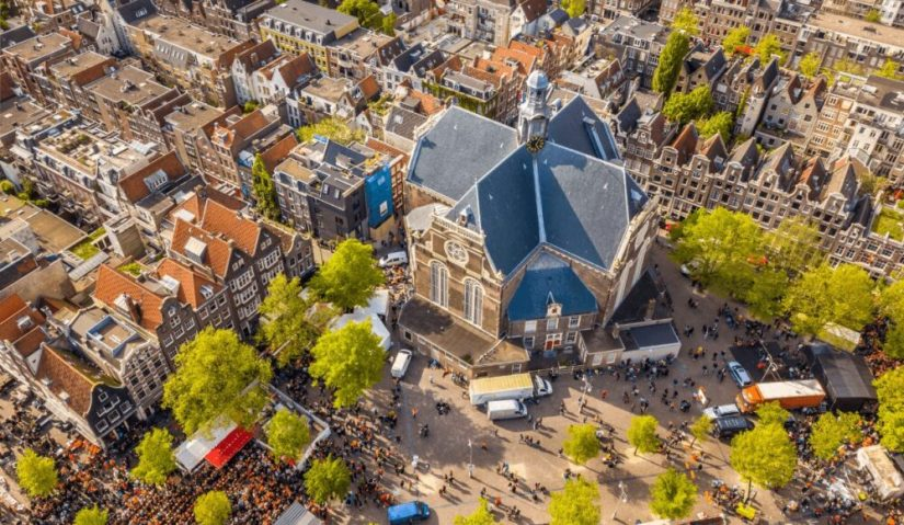 Aerial view of the Noordemarket with a large church-like building and smaller houses in the traditional Dutch style around it.