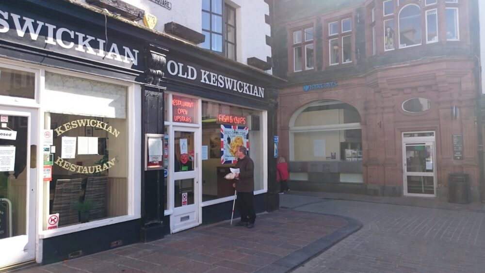 """A traditional high street in England with a man looking inside the restaurant that says """"Old Keswickian"""" and has posters for fish and chips."""