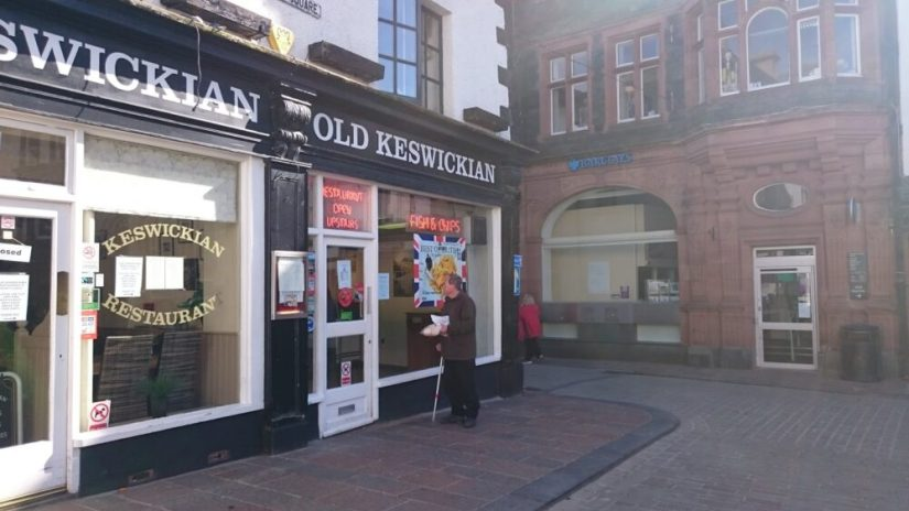 "A traditional high street in England with a man looking inside the restaurant that says ""Old Keswickian"" and has posters for fish and chips."
