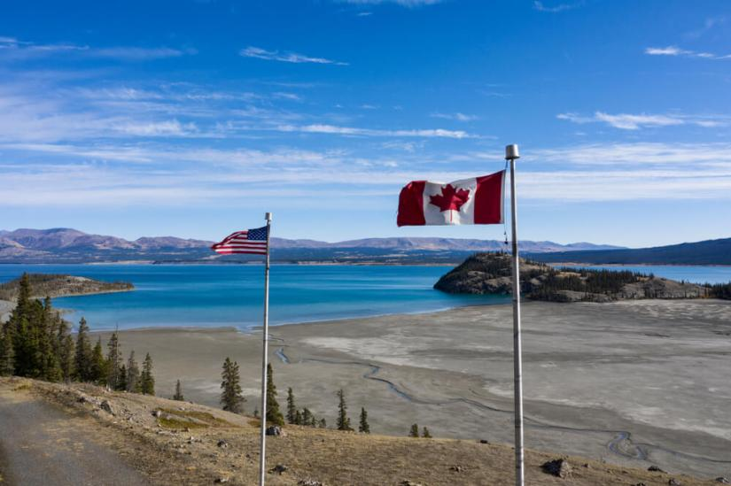 An American and a Canadian flag side by side next to barren fields and a deep blue lake while driving the Alcan Highway road trip to Alaska