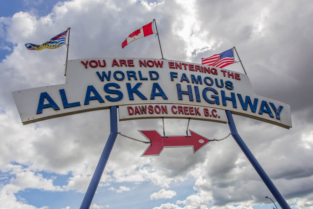 """Sign with three flags reading """"You are now entering the World Famous Alaska Highway Dawson Creek BC"""""""