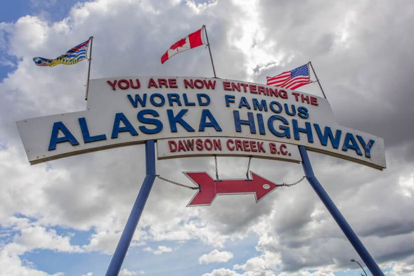 "Sign with three flags reading ""You are now entering the World Famous Alaska Highway Dawson Creek BC"""