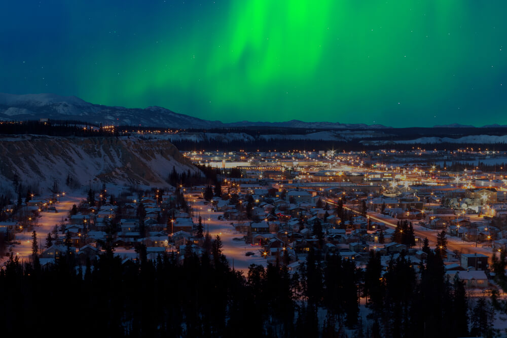 Green Northern lights above the lights of the town of Whitehorse, Yukon in Canada along the AlCan Highway