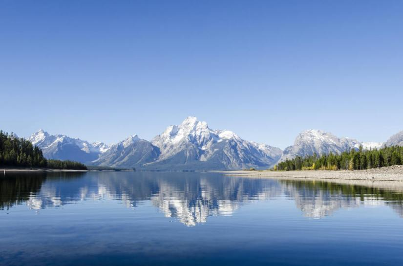 A mostly still lake reflecting the mountains of the Teton Range beautifully in its glassy, slightly rippled surface.