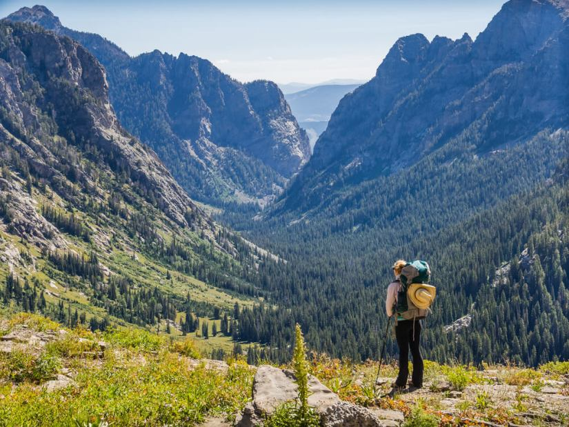 A female hiker looking at a valley in Grand Teton National Park, well-prepared with a backpack, hiking poles, and a sunhat on her back.