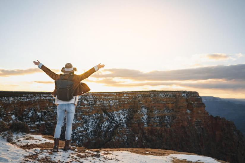 Woman wearing hat, jacket, jeans, and snow boots at the Grand Canyon in winter, with her arms up in the air as the sun sets.