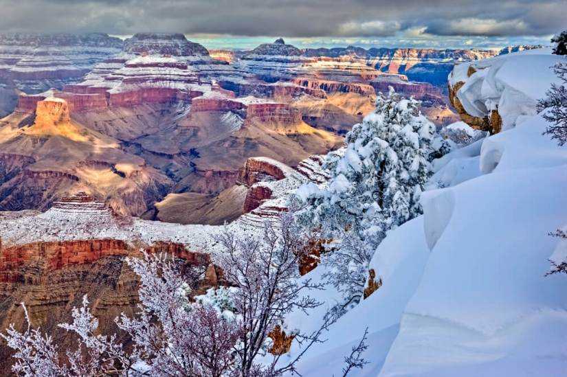 Winter landscape at the Grand Canyon, white snow blanketing the higher elevation pockets of the park and tops of the mesas, and the valley below showing red rock and orange rocks