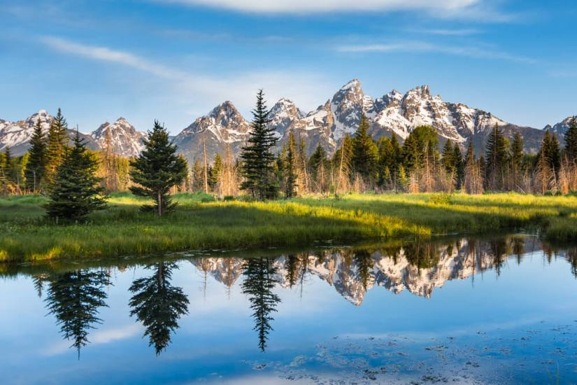 Mountain peaks of the Teton Range reflecting perfectly in still lake water on a sunny day in Grand Teton National park