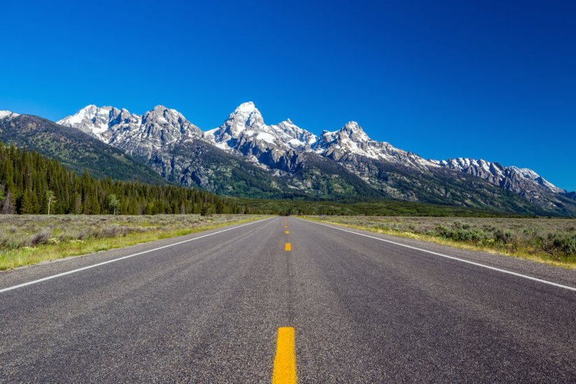 An empty road leading towards the distinctive peaks of the Teton Range near Grand Teton National Park on a cloudless summer day.