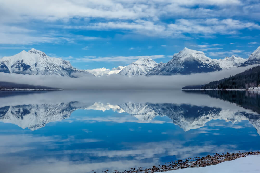 The unfrozen surface of Lake McDonald in early winter in Glacier National Park, reflecting the snow-covered mountains with a patch of fog on a sunny winter day.