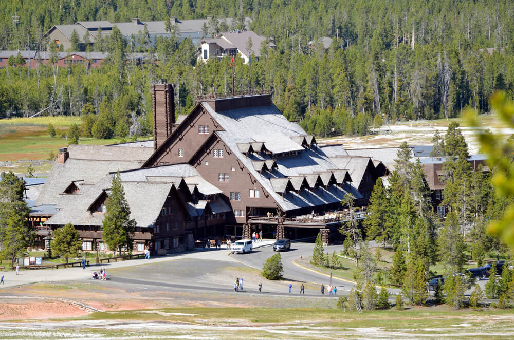 Old Faithful Lodge near the geyser, a large wooden mountain lodge surrounded by trees, a popular place to stay on a Yellowstone road trip