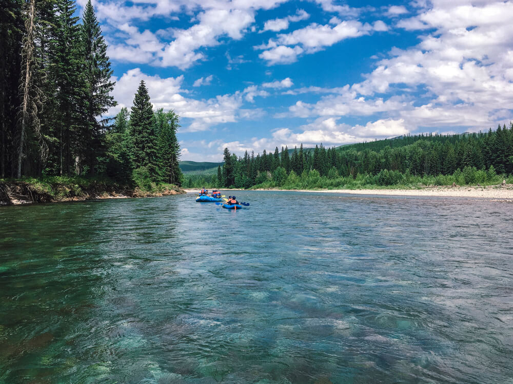 Two rafts ahead on the Flathead River, which is calm, turquoise and surrounded by trees and hills on a sunny day in Glacier National park