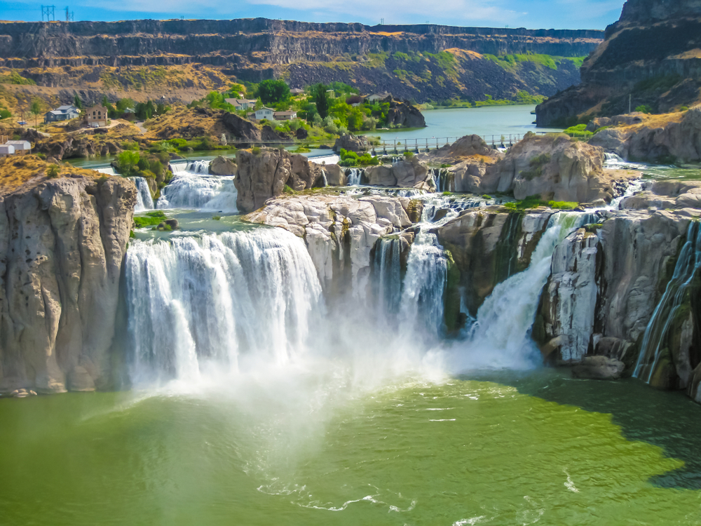 The waterfalls of Shoshone Falls cascading in a horseshoe shape over a large cliff edge, tumbling into a pale green pool of water below, surrounded by a rocky landscape.