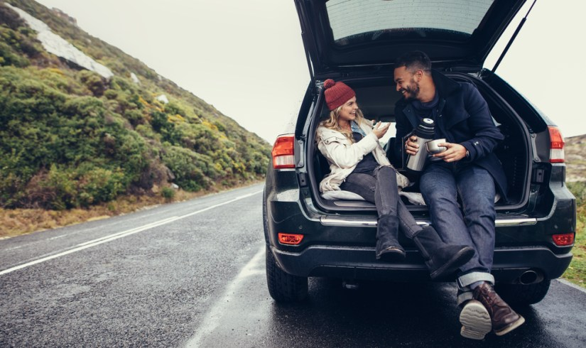 Interracial couple (white woman and Black man) sharing a thermos of coffee while pulled over on the road while wearing cold-weather clothing, sitting in the back of their car.