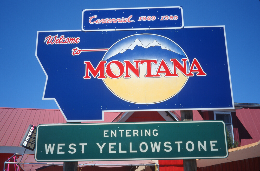 """Sign that reads """"Welcome to Montana, entering West Yellowstone""""."""