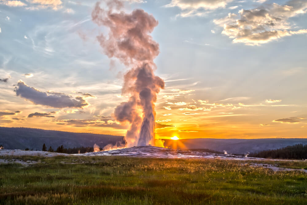The Old Faithful geyser at sunset, a plume of steam shooting high into the air as the sun sets behind it, a classic sight on any Yellowstone itinerary.