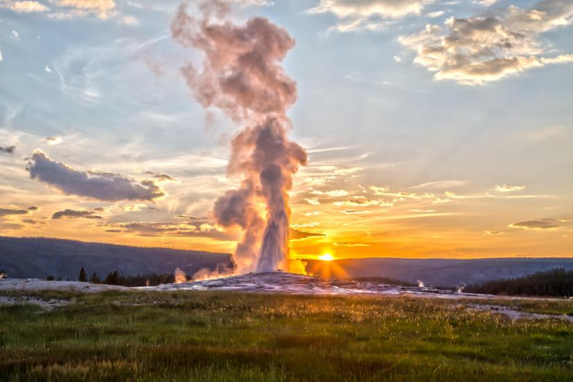 The sunset at Old Faithful, a geyser spouting into the air with the setting sun showing up in a sunburst behind the geyser in Yellowstone National Park