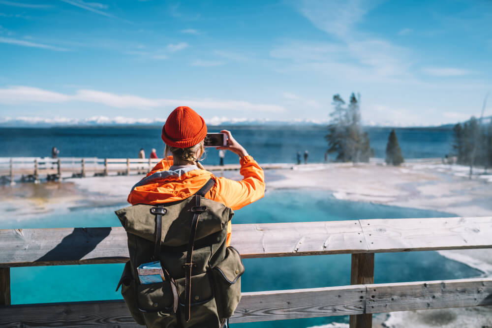 A woman wearing an orange hat and orange rain jacket and a backpack taking cellphone photos at one of the hot springs in Yellowstone by a lake.