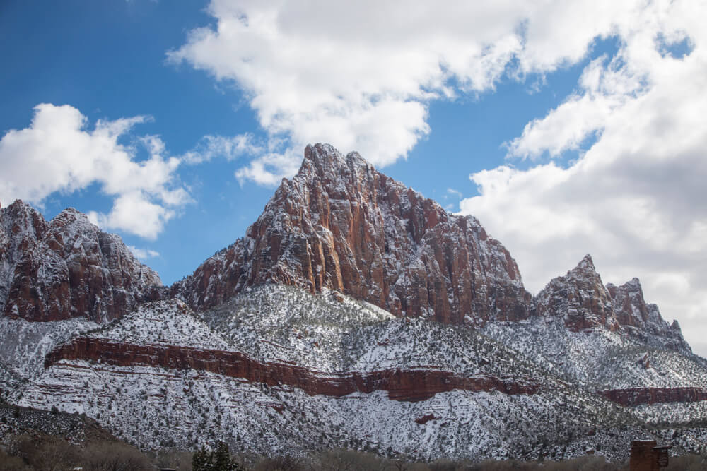 Snow-covered mountain near the Watchman Campground, with a partly cloudy sky in the background. Red rock showing behind the snow.