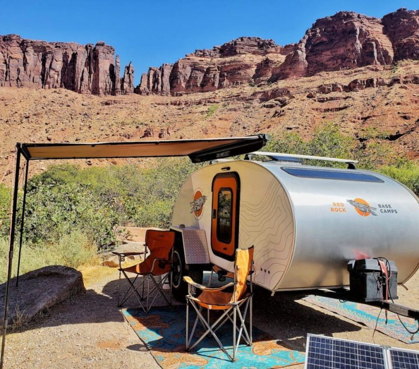 A silver teardrop trailer with an awning over it, with two orange camping chairs, next to a solar panel in a beautiful red rock landscape typical of Moab.