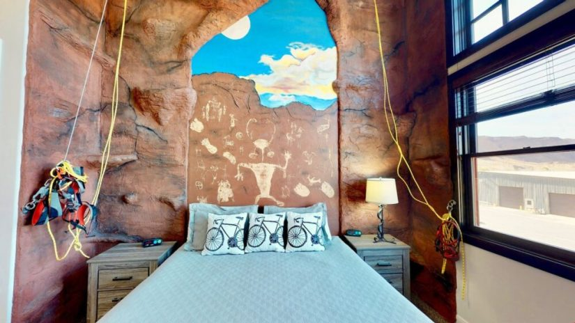 Unique Moab Airbnb concept: a bed with a wall at the headboard showing rock paintings, with rock climbing gear and notches in the wall to try out rock climbing on.
